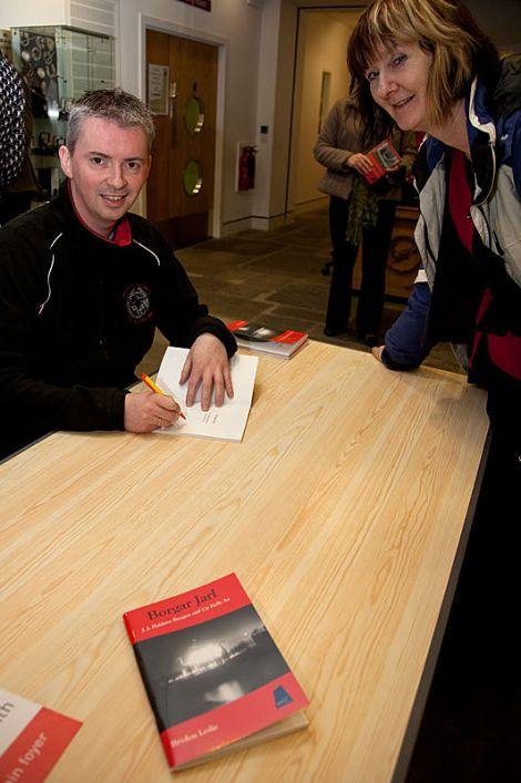 Brydon Leslie signing a copy of his book on Up Helly Aa founder JJ Haldane Burgess for Shetland archaeologist Val Turner.