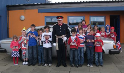 Lord Lieutenant Bobby Hunter and all 15 Nesting primary pupils who gave up a day off school for the jubilee celebrations. Behind them is Philip Gifford's silver Volvo hot from the Classic Motor Show. The same car starred in Shetland's silver jubilee celebrations in 1977. Pic. Kate Coutts