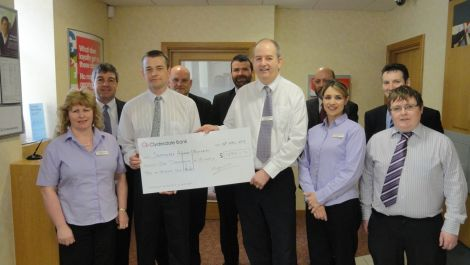 Lerwick Clydesdale Bank manager Rod MacLeod hands the large cheque over to Jim Livitt of the memorial committee. Back (from left): Robbie Leask, Alistair Carnie, Steve Knowles, Andy Forteath, David Coles. Front: Angela Duncan, Jim Livitt, Rod MacLeod, Shannon Moreland and Chris Duncan. Absent from the photo is Craig Spowart.