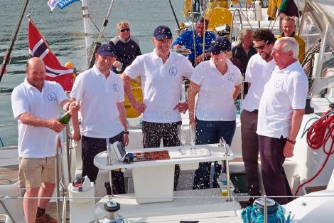 Celebrating victory are the crew of the Erin with crew member Ken Brown opening the champagne - Photo: Chris Brown