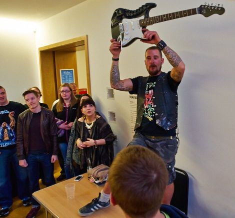Dirk Robertson waves his coveted hand-carved guitar during the raffle. Photo Chris Brown