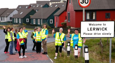 Happy faces as Liz reaches the Welcome to Lerwick sign on the old North Road. Photo: Barry Broadbent