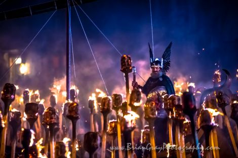 Guizer Jarl Olav Haraldsson cuts a spectacular figure as the torches give the night air a beautiful hue. Photo: Brian Gray