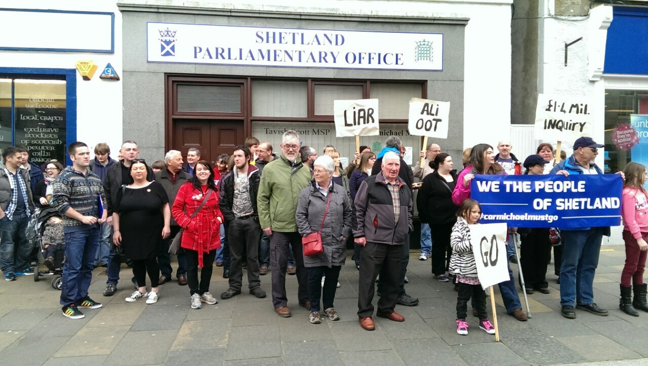 Protesters gather outside Alistair Carmichael's constituency office on Saturday afternoon to call for his resignation. Photo Shetnews