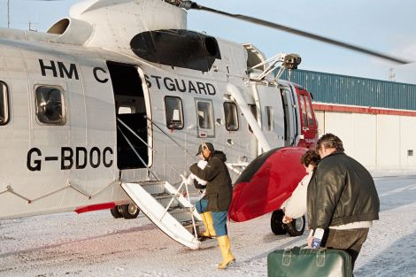 Aith couple Laureen and Gordon Hay with their newborn daughter Lindsey boarding the coastguard helicopter Oscar Charlie at Sumburgh.
