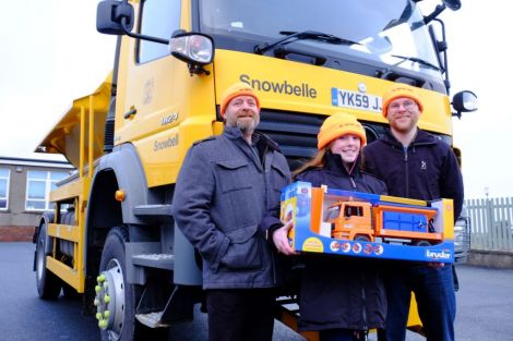 For her winning gritter name 'Snowbelle', Olivia Campbell (centre) from Bell's Brae Primary School received a model snowplough, goody bag and 'gritter crew' hat from councillors Michael Stout (left) and Steven Coutts. Photo: SIC