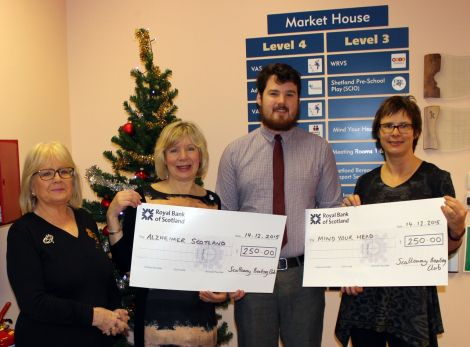 Toby Sandison of Scalloway Boating Club presenting cheques to Mind Your Head and the Shetland branch of Alzheimer Scotland.