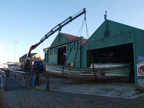 Being lifted into the museum's boat store to be refurbished. Photo Shetland Museum and Archives