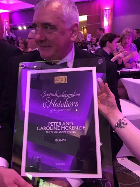 Peter Mackenzie holds up the award he and his wife Caroline won on Sunday night.
