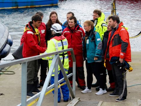 The crew being met by Shetland coastguard officers when they arrived in Scalloway, before being interviewed by the police about their experience and being taken to emergency accommodation. Photo Chris Cope/Shetnews
