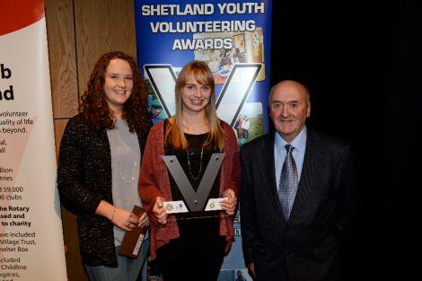 Kaylee Mouat and Lauren Smith from Shetland Junior Netball Development Group, with Alec Miller of Voluntary Action Shetland.