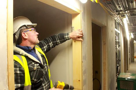 Door hinges are being put in place at one of the bedrooms in the halls of residence.