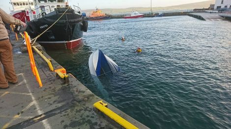 The overturned boat shortly before being lifted from the harbour - Photo: Caroline Watt/Shetland News