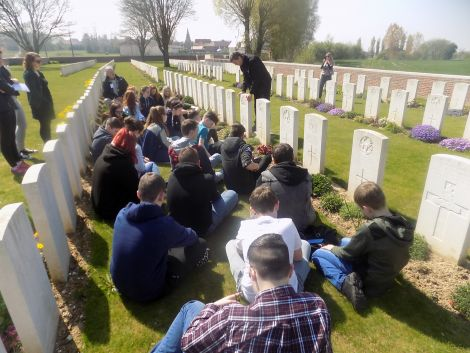Pupils listening to a tour guide at Dartmoor Cemetery on the Somme.
