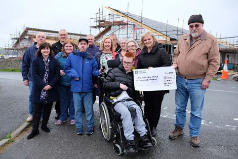 John Hunter, Chair of Shetland Special Needs Action Group (right), presents a cheque for £10,000 to Connie Russell, Team Leader – Eric Gray Resource Centre, towards the Hansel Fund for the new building. Back row (l to r) – Chris Pulley, Neil Risk, Kenny Groat, Davy Napier, Thelma Leslie. Front row: Janne Glesnes Martin (EGRC), Katie Hunter, Paul Ditchburn, May MacDonald, Doreen Williamson, Connie Russell and John Hunter. Centre Front – Dylan McDougal. Photo: SIC