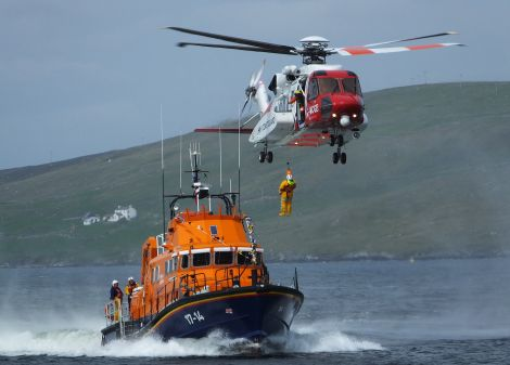 Crew from the coastguard helicopter, pictured on a training exercise with the Aith lifeboat, will take part in a wreath laying ceremony alongside colleagues from the Lerwick lifeboat. Photo: Bristow Helicopters