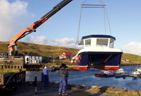 The new catamaran is slowly lifted into the water at the Vidlin marina on Thursday. Photos: Hans J Marter/Shetland News