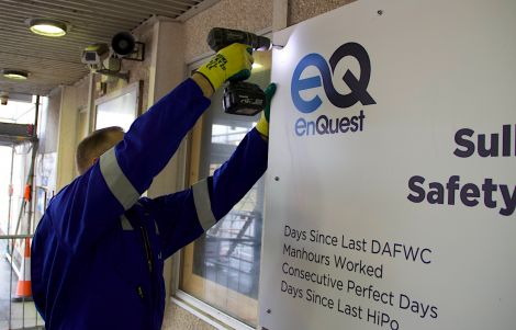 All change at SVT: a DITT worker replaces a BP safety sign with EnQuest's own branding.