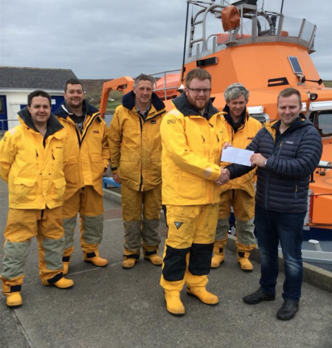 Captain Marius Joensen presenting the cheque to crew member John Robertson. Also pictured, left to right, are Allan Willmore, Chris Smith, David Nicolson and Luke Bullough. Missing from picture are Lewis Fraser and Pete Hanscombe. Photo: RNLI/Liz Boxwell